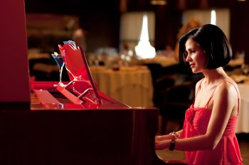 beautiful brunette woman red dress playing piano