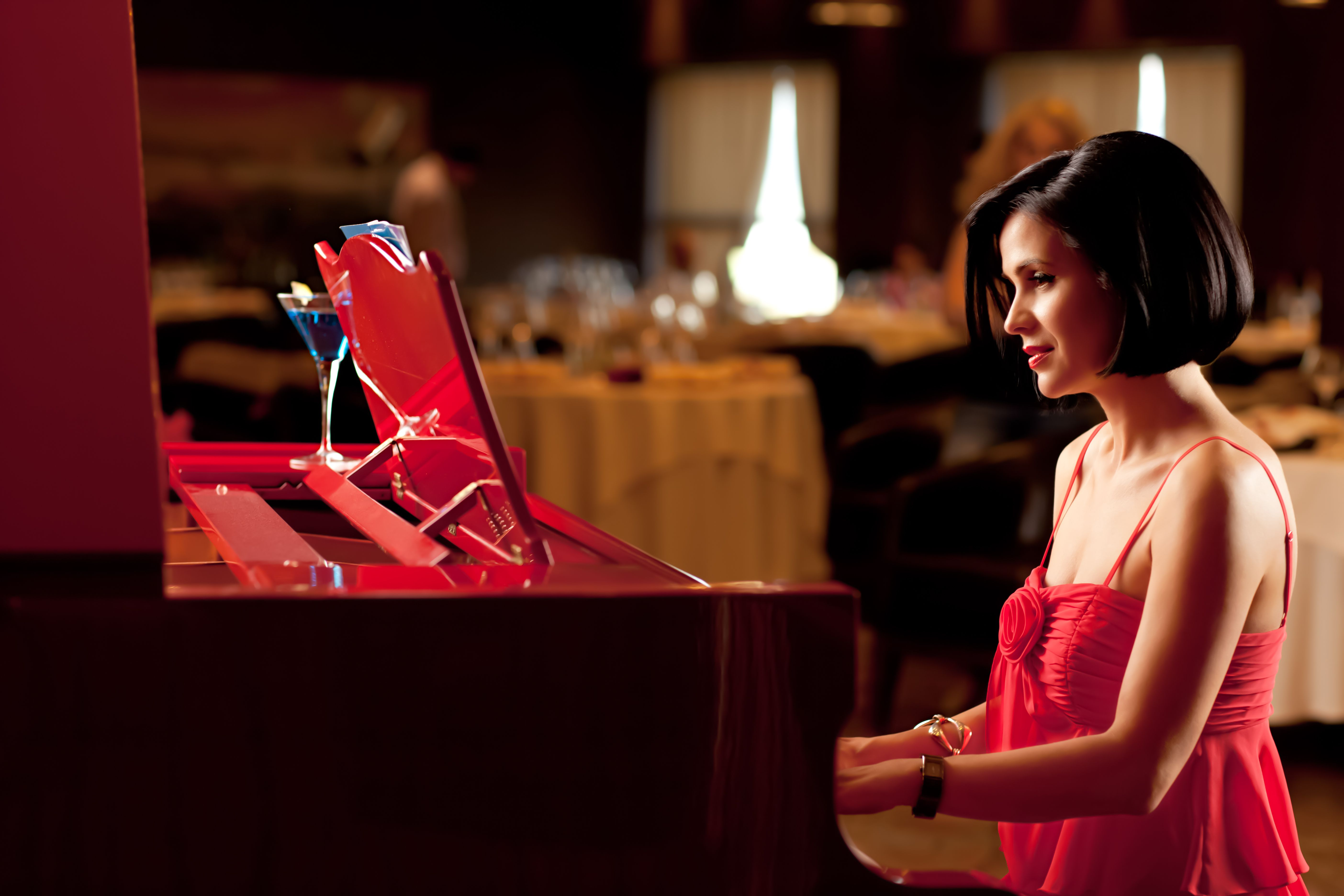 beautiful brunette woman red dress playing piano